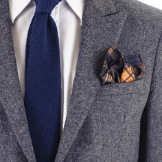 A bold tartan check silk pocket square in navy blue and amber, accented with a hint of green, is the perfect foil for navy tailoring. Handmade in Italy from 100