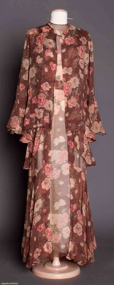 """JEAN PATOU SILK CHIFFON GOWN, 1935. Long gown & matching jacket & belt, cocoa brown w/ white & red blossom print, bias cut dress w/ shoulder & hip flounces & streamers, jacket slightly fitted w/ fluted sleeves, label """"Jean Patou Cannes, Monte Carlo Biarritz 7 Rue St. Florentin Paris"""". Front"""