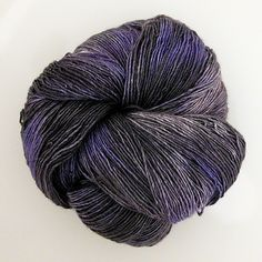 """Shimmery and energized singles yarn.  This is a semi-solid very dark grey with a single color accent that is part  of the """"Croton"""" series.  70% Superwash Merino, 30% Silk  438 yards/400 meters  100g"""