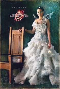 there is so much symbolism  Katniss not sitting in the chair, because she doesn't abide by the Capitols rules  -She is the only one so far looking directly at us to show that she isn't intimidated by the Capitol, but the others were.  -Shes holding the white rose down to show her feelings of superiority over it with President Snow being the rose.  -Unlike the others Katniss has a simple and plain chair. It's because Katniss was a simple girl from The Seam who became the symbol of the rebellion.