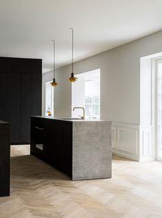 Parquet en pointe de hongrie - cuisine noire - ilot en pierre - accessoires en laiton - suspensions de designer - style minimaliste et canon
