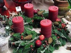 Adventkranz rote Kerzen mit Zapfen, Ästen Beeren Äpfel
