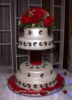 Torta de Boda color Blanca nacarada con detalles arabescos en negro, unidas con una base de vidrio. Decorada con Rosas Rojas