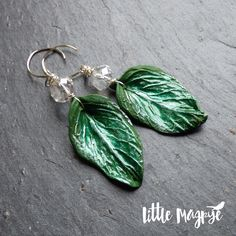"""Spring Greens"" – Large fresh green polymer clay leaves by UK Artisan Joanne Louvaine Bell of Twinkiedinky, sparkling clear faceted rondelles, silver plated wire and the lovely Annie Nowak's earhooks. A simple mix that is both substantial and stylish. The leaves made me think of lush, freshly picked spring green cabbage, hence the name. 7.5cm...  Read more »"
