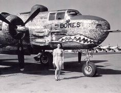bomber with the name 'Bones' and shark's teeth painted on it. A woman in day clothes stands in front of the plane, and there is a row of other planes extending off into the background distance. Ww2 Aircraft, Fighter Aircraft, Military Aircraft, Aviation Image, Aviation Art, Airplane Art, Ww2 Planes, Fire Powers, Nose Art