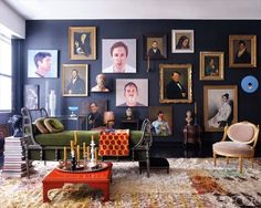 Portraits on black wall, deep olive green daybed, glossy red coffee table, light colored carpet. Polished bohemian.