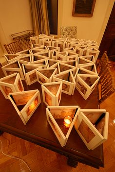 Cheap frames, spraypaint, and ducktape (I think I would use white to match the frames). Print photos on vellum, and staple or tape them into the frame. Place a candle in the middle for a personalized, glowing centerpiece. Cute!