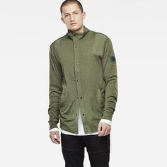 This military-inspired piece combines a tall collar and snap closure with tough twill patches on the shoulders and arms.