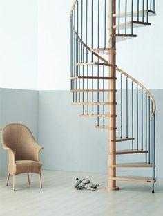 escalier design en forme de coquillage, marches étroites, fauteuil tressé en couleur beige avec des pieds hauts, garde corps en bois noir et beige, effets barreaux fins