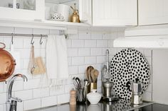 Copper and gold accent pieces add elegance to a white and stainless steel kitchen.
