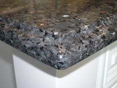 Black & grey granite countertop paired with white cabinets More