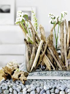 lovely driftwood in a glass vase paired with white flowers and pebbles - perfect for a beach themed tablescape