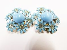 """Vintage Pastel Blue Enamel Flower Clip on Earrings.  These earrings feature a hard plastic bead in a pastel blue with a cluster of daisy like flowers around them.  The little flowers are enameled metal.  They have a rhinestone center.  The earrings are approx. 1 1/8"""".  They are in good condition with some wear to the enamel."""