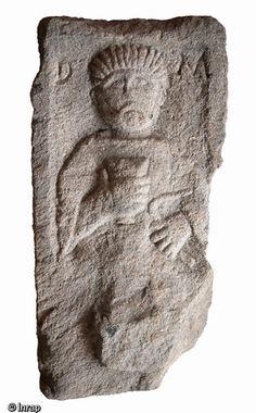 Stèle funéraire gallo-romain en arkose (hauteur 80 cm, largeur 41 cm), première moitié du IIe s. de notre ère, nécropole de Pont-l'Évêque,Autun. La main droite du personnage présente un gobelet tandis que la gauche tient un objet mince et courbé, interprété comme une enclume mobile, attribut d'un artisan du métal...