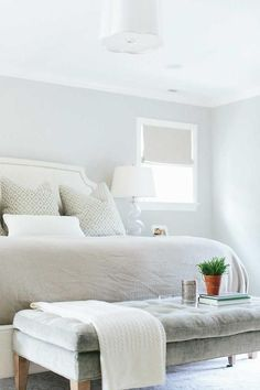 Sophisticated bedroom features a gray wall lined with a white headboard with brass trim on bed dressed in white and gray pillows next to a nightstand topped with clear glass Gourd Bedside Lamp situated under small square windows dressed in gray roman shade alongside a gray velvet tufted bench placed at the foot of the bed illuminated by a Barbara Barry Simple Scallop Pendant.