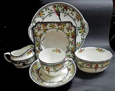 Doulton deco: unnamed teaset incl tea trio and cake plate, H2637, c1925 (pattern). Vivid multi-coloured parrots perched on monochromatic framed border with yellow and pink flowers and green branched foliage, including small floral motif to inner rims, and black twisted cup handle, highlights and trim.