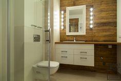 Aranżacja łazienki w nowoczesnym stylu. Dekoracyjne żarówki wokół lustra umieszczone na drewnianej ścianie tworzą niesamowity efekt. Drewniane elementy z białymi płytkami to sprawdzony duet. Toilet, Mirror, Bathroom, Furniture, Home Decor, Washroom, Flush Toilet, Decoration Home, Room Decor