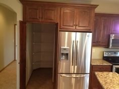 Walk-in pantry behind the fridge!! Such a good idea! by meghan