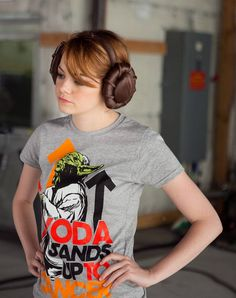 "Lucasfilm, eBay and Major League Baseball – as well as assorted celebrities – have teamed up to help raise funds for the non-profit organization Stand Up To Cancer (SU2C).  Here, Emma Stone sports a Yoda ""Stand Up 2 Cancer"" T-shirt while wearing Princess Leia ear muffs on her head."