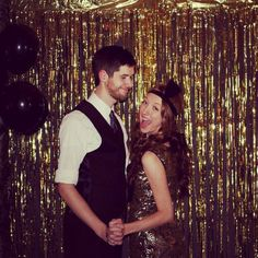 Black sheet, gold tinsel, black balloons. Great gatsby theme photo booth backdrop.