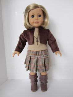 This warm brown plaid skirt is made of heavy flannel. The dark brown cropped jacket is constructed of no-whale corduroy. A tan short sleeve knit top is underneath. An antique gold key necklace blends with the browns. To finish her attire, Kit has chosen milk chocolate brown fringed boots.