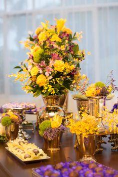 Mesa de doces de casamento com flores amarelas e roxas. Peças em dourado e prateado. #limoeirodecor #wedding