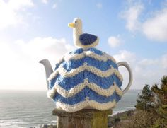 Knitted Cornish tea cosy, This seagull tea cosy is at home by the sea, or in your home. This is a nautical knitted tea cosy in a cornishware style seaside design, with a crochet seagull on top. It fits a standard 4-6 cup (2- UK pint, 40 fl oz) teapot. Inspired by the sea, waves and gulls that are all around us in Cornwall. The tea cosy is knitted in blue and cream thick chunky wool, making it very warm and cosy for your teapot. This cute seagull looks fantastic in a kitchen, on the dining…