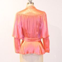 Highly collectible Ossie Clark for Radley vintage 70s pink satin blouse offered by DaisyandStella! This vintage designer blouse from Ossie Clark for Radley, is made of luxurious pink satin styled with a risque plunging cutout keyhole bodice with a double buttoned neck and waist,