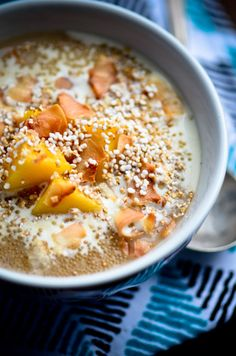 amaranth porridge with mangoes and coconut.  1/2 cup amaranth plus 2 tablespoons,  1 cup lite coconut milk,  1/4 teaspoon cinnamon,  1/8 teaspoon ground cardamom,  1 inch piece of ginger,  2 tablespoons maple syrup,  1 vanilla bean,  pinch of sea salt,  1/4 cup toasted coconut,  1/2 cup diced mango,  extra coconut milk for serving