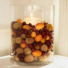 Fall centerpiece - Heaped with walnuts, cranberries, and kumquats, a cylinder vase displays festive flavors. Place a tall to pillar candle and holder inside the vase; surround with fruits and nuts. Decoration Christmas, Decoration Table, Candle Decorations, Edible Centerpieces, Centrepieces, Centerpiece Ideas, Thanksgiving Table, Thanksgiving Decorations, Seasonal Decor