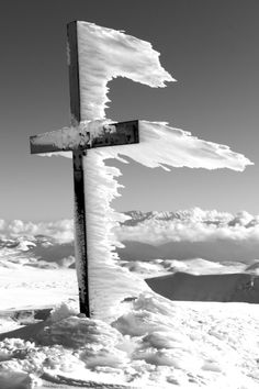 Cross with frozen snow blown in the wind.