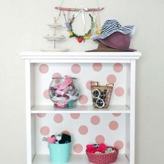 Turn a bookcase into a girl's accessory holder. Don't forget to add polka dot wall decals to the back as a finishing touch!