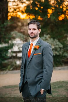 Dark gray suit, bright orange tie, kerchief, and boutonniere