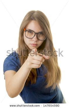Young woman with glasses point at observer. Focus on finger - stock photo