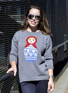 An oversized high-low sweater featuring a Russian Doll graphic.