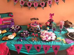 """Monster High party table for my daughter's 5th. Combination of hot pink, turquoise and black- black table cover on bottom, turquoise table cover on top swagged and pinned with hot pink bows on each corner. Bows were made with bath poufs!!! Used zebra print banner and stuck letters to spell """"happy birthday"""". Lollipop spiders, marshmallow ghosts, Oreo spiders, snack served on bat trays. Her birthday is in November so got Halloween decorations on sale."""