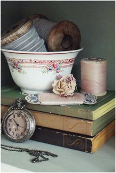 Antiques - pretty bowl used to hold useful items elevated on a stack of books including the antique watch for more interest.