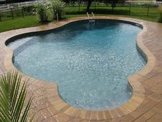 free form vinyl liner with color coordinated steps, vinyl covered shallow end bench, brick coping and paver patio