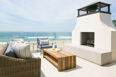 Seaside deck features a wicker sofa facing a teak waterfall coffee table and a stucco outdoor fireplace accented with a black herringbone firebox finished with a glass railing.