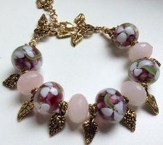 Classy charm bracelet made with millefiori glass beads, quartz and Tibetan style pendants.