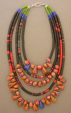 "Dorje Designs | Five descending strands of multi-colored African vulcanite heishi beads,  from 16.5"" to 26.5"" long, are finished with green glass beads, Russian blues,  and modern reproductions of rare kiffa beads. 