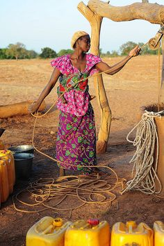 African woman getting water in the sweet light before sunset by luca.gargano, via Flickr