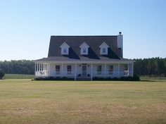 Beautiful country home with amazing front porch...Needs shrubbery and trees.