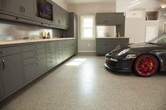 Dark grey Porsche with red racing rims in a garage with a beautiful garage floor coating.