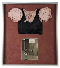 "Costume Worn by Shirley Temple in the 1933 Film ""The Kid's Last Fight"" The two-piece ensemble comprises a peach silk blouse with black polka dots and large bow at the center neckline, under a black silk satin vest. The costume was worn by Shirley Temple in the early 1933 one-reeler satire ""The Kid's Last Fight"". A vintage photograph of Shirley wearing the costume is included. The costume was sewn for Shirley by her mother, Gertrude Temple. Z"