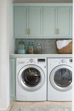 Gray green shaker cabinets adorned with brass pulls hang over a gray mosaic tile backsplash and an enclosed washer and dryer.