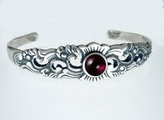 Sterling Silver Floral Cuff Bracelet Accented with Genuine Garnet The Silver Dragon- Bracelets. $105.00. This Unique Bracelet is Created only after Your Order Arrives. Please Allow 7-10 days for Delivery.. Designed And Hand- Crafted in Sterling Silver. The Silver Dragon uses Sterling Silver that has been Reclaimed... Helping Save Mother Earth's Resources.. This Bracelet Fits a Standard Woman's Wrist. This Bracelet was Designed by The Silver Dragon, a Jewelry Sh...