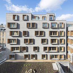 Boxy windows puncture grey brick walls at this Paris development by French architect Michel Guthmann, containing social housing, a hostel and a cinema..