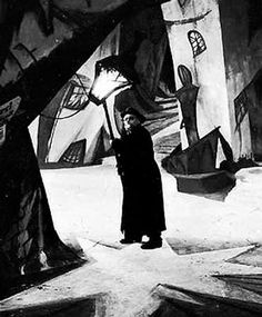 German Expressionism.  In this image it's referring to the film movement in the 1920s where a lot of German filmmakers saw the strong link between architecture and art.  This is a still from The Cabinet of Dr. Caligari (1920), and the strong angles and sense of monumentalism that characterised German Expressionist film can be clearly seen.