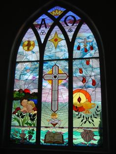 image of Cross on which the Messiah died and Biblical symbols around the cross.   Stained Glass Window